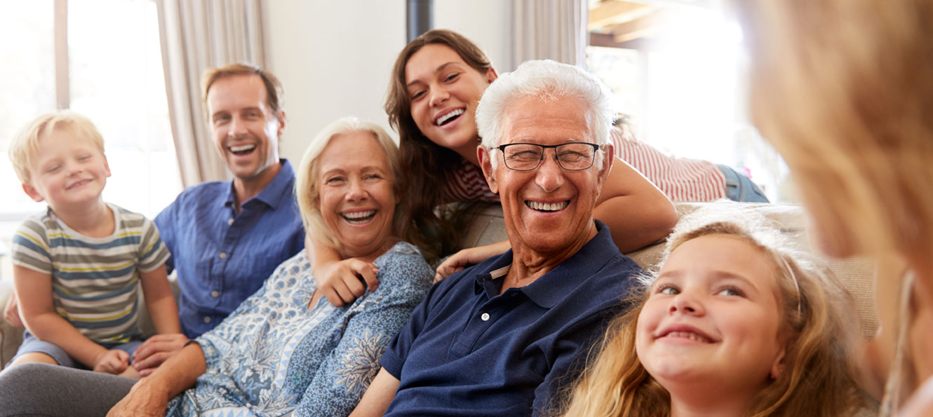 extended family sitting together in a living room and smiling at each other