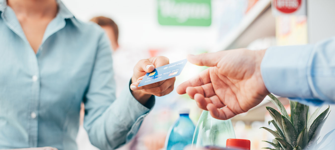closeup of hand holding a credit card while making a store purchase