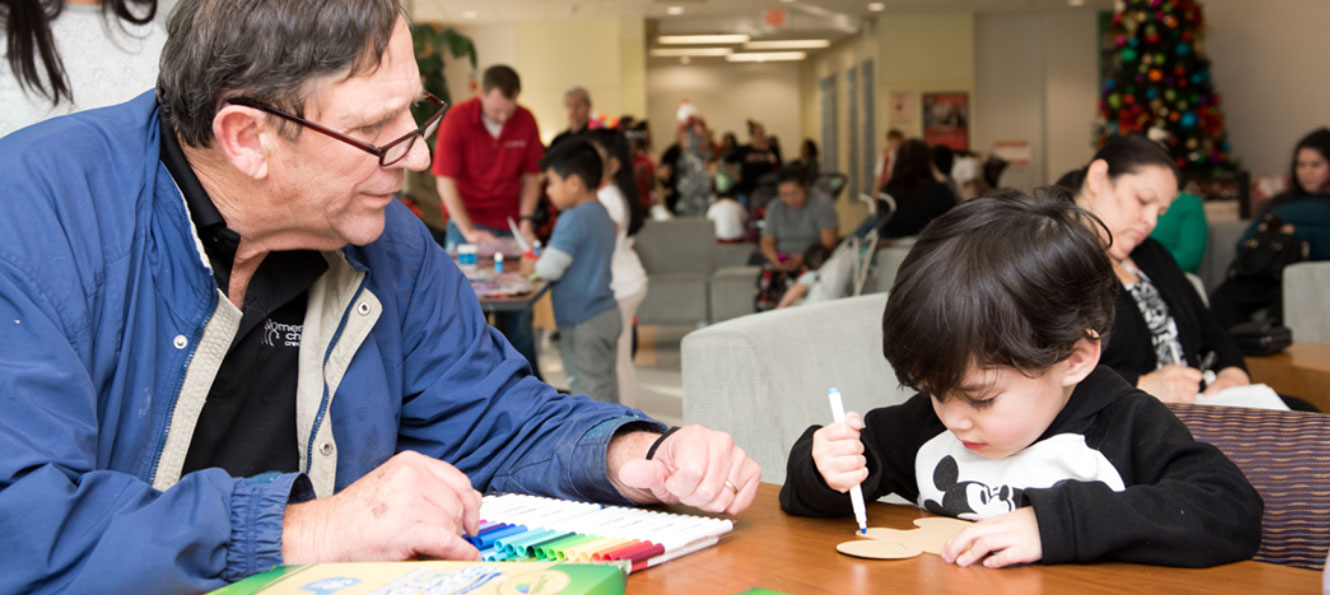 a Members Choice employee volunteers with a young child coloring at a community event