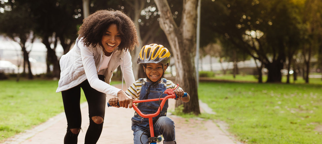 mother helping young son learn how to ride his bike