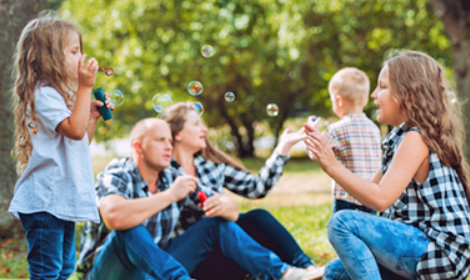 family of five blowing bubbles in an outdoor park