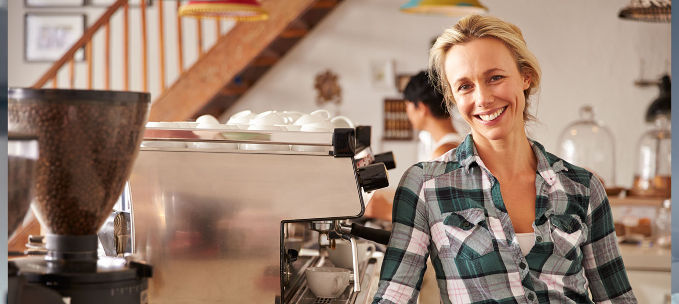 portrait of a business owner smiling in her coffee shop