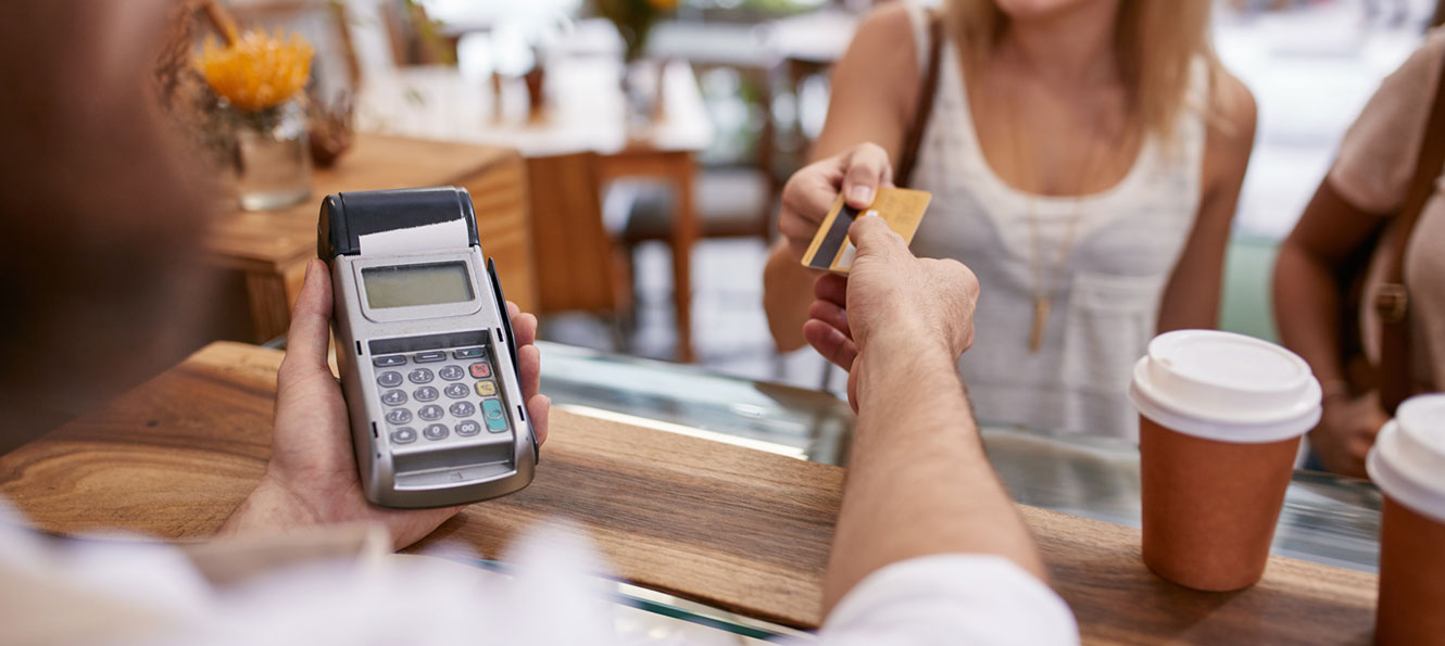 woman using a debit card to pay for coffee