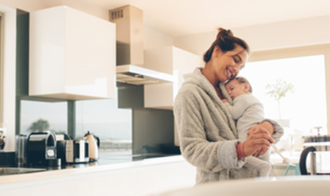 mother holding baby while she makes herself coffee in the morning
