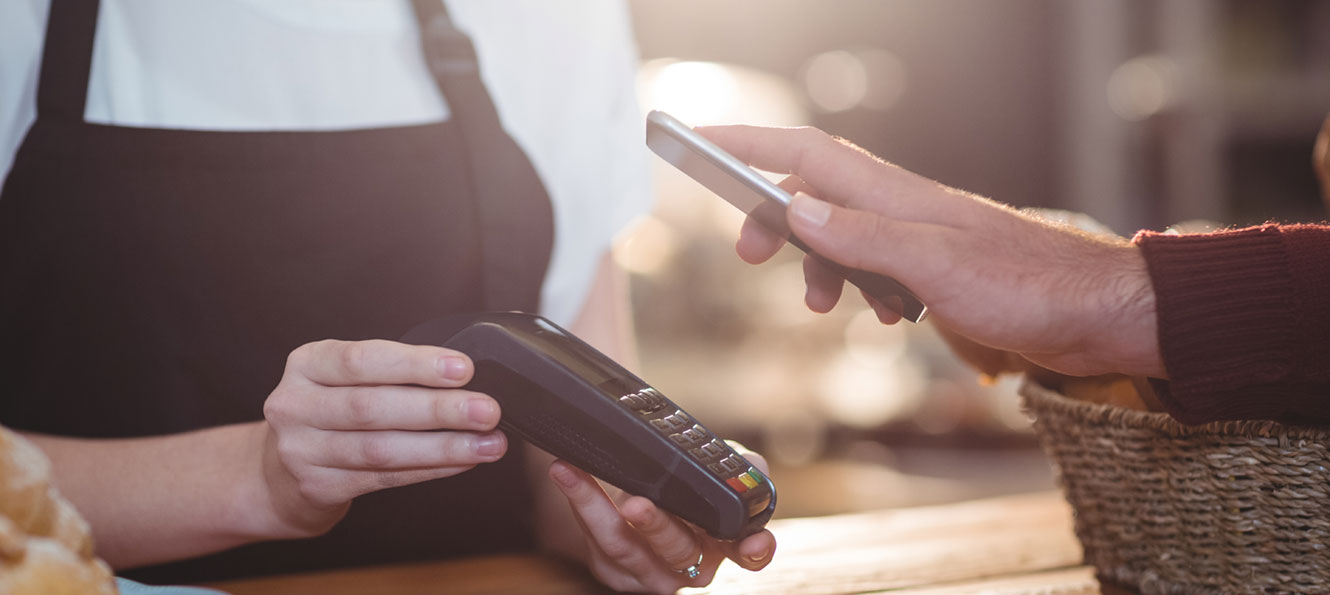 hand holding smartphone over a payment terminal to pay with their digital wallet app