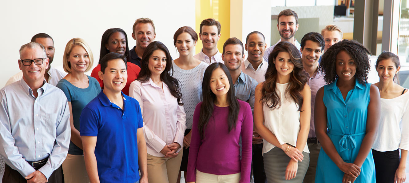 group of smiling employees standing in the lobby as part of a group shot together
