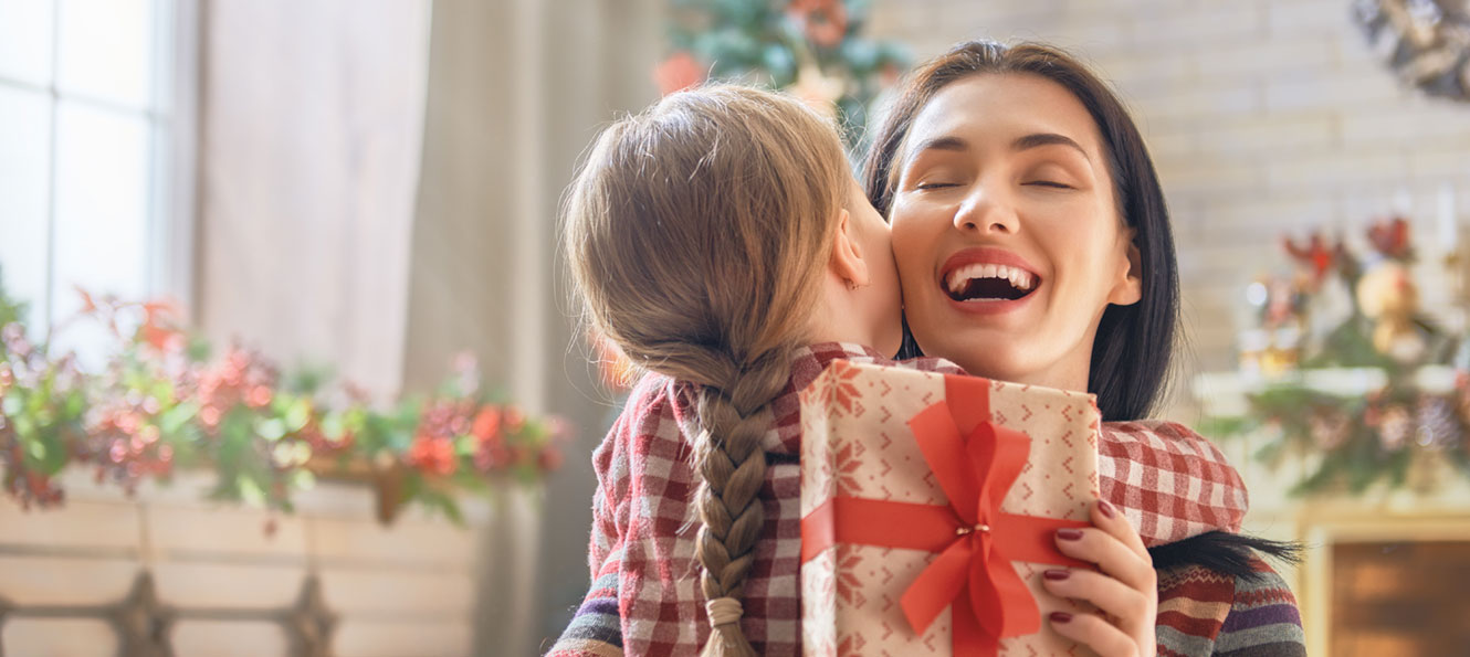 woman hugging a child while holding a gift in a holiday setting