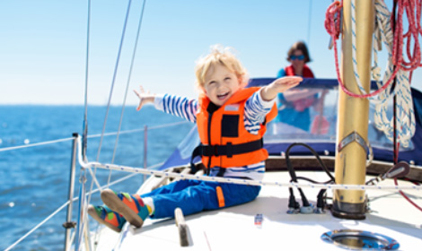 young child smiling and wearing a bright orange safety vest on the deck of a boat
