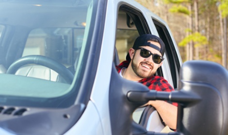 guy wearing sunglasses sitting in the drivers seat of his truck